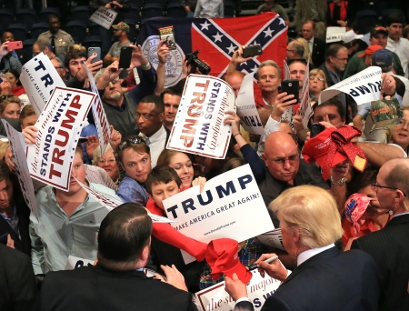 Republican presidential candidate Donald Trump works the crowd at the conclusion of his second campaign visit to Georgia at the Macon Centreplex Coliseum while a member of the crowd holds up the former flag of the state on Monday, Nov. 30, 2015, in Macon, Ga.  (Curtis Compton/Atlanta Journal-Constitution via AP)